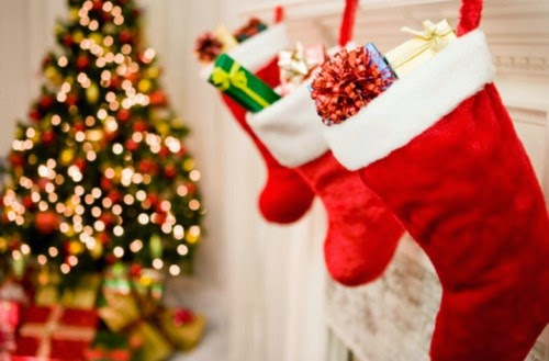 3 hanging stockings on a fireplace with a Christmas tree with fairy lights and presents underneath blurred in the background