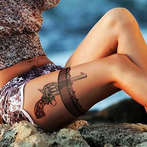 kadın üst bacak jartiyer ve silah dövmesi woman thigh gun and garter tattoo