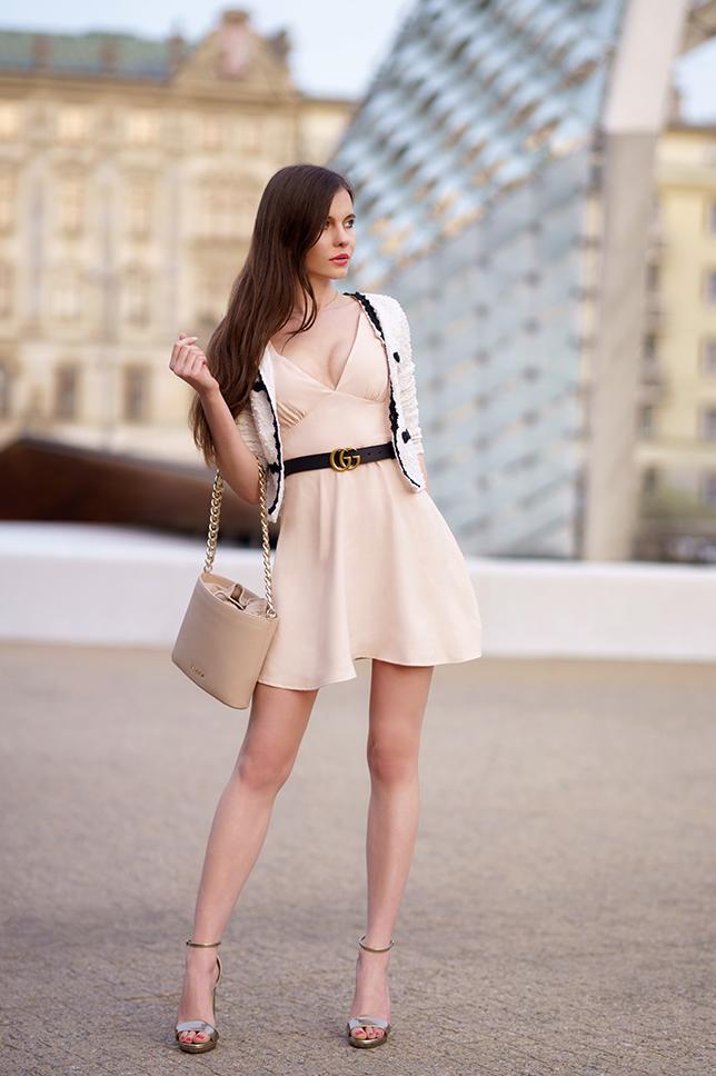 Biały cardigan, beżowa sukienka i złote sandały na obcasie