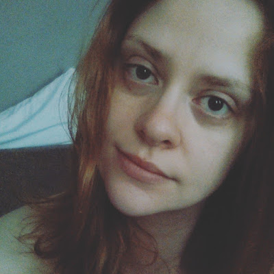 an unedited selfie a person with dark eyes and red hair