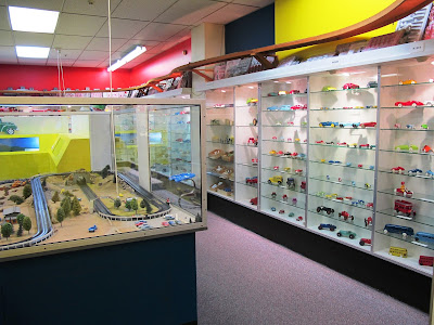 Rows of metal cars displayed on shelves in glass cabinets lining the walls. In the front left is a slot-car set up under perspex.