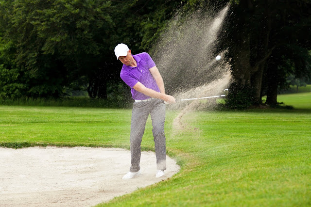 Golfer getting out of a bunker playing hazard
