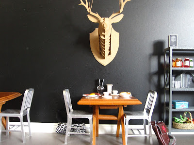 Corner of a modern one-twelfth scale miniature cafe with a black wall and a cardboard stag head mounted on it. Underneath it is a table set for breakfast.