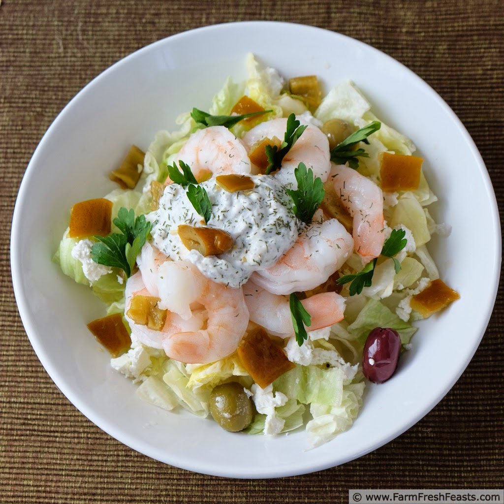 image of a bowl of Mediterranean shrimp salad with spiced Greek yogurt, served over lettuce with olives and feta