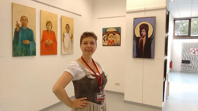 Künstlerin Olga David mit ihren Bildern im Hintergrund