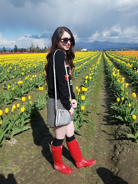 spring skirt outfit with red rain boots