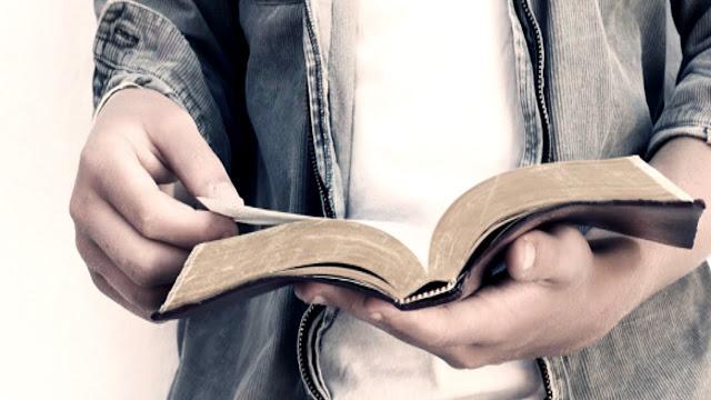 Rapaz segurando uma bíblia aberta