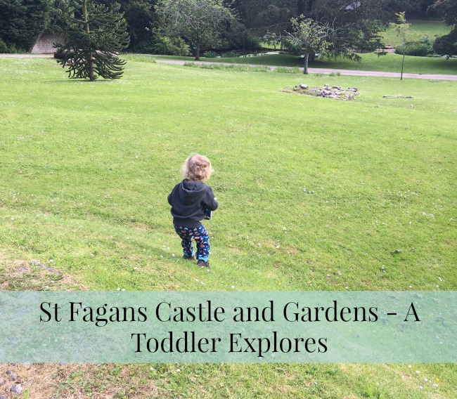 St-Fagans-Castle-and-Gardens-A-Toddler-Explores-text-toddler-on-grass