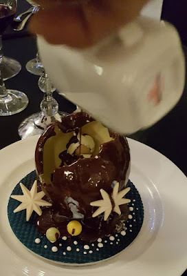 Pour warm chocolate sauce over the Silent Night Sphere until the chocolate melts.