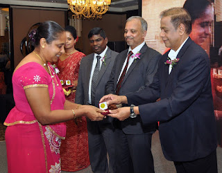 Chairman of the People's Bank Hemasiri Fernando, Chief Executive Officer/General Manager of People's Bank, N. Vasantha Kumar and Deputy General Manager of Human Resources S. A. R. S. Samaraweera presents a token to one of the 94 long-serving employees who were felicitated at the event.