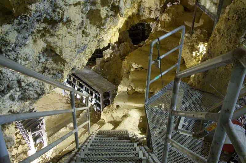 stairs and railings going down into cave