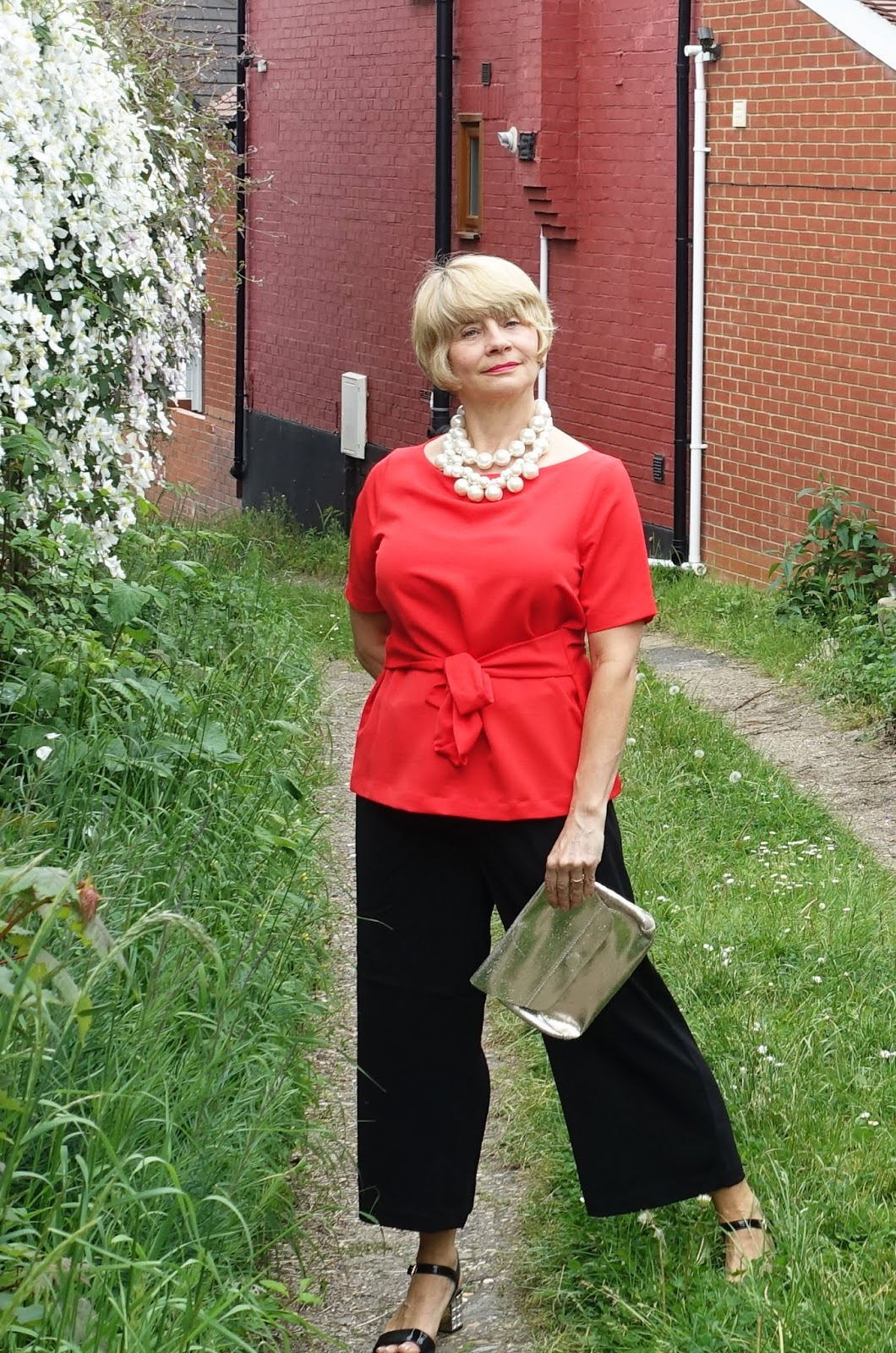 In part two of a special on how older women can wear summer 2018's cropped and wide trousers, Is This Mutton dresses up a pair of black trousers with a red top and pearls.
