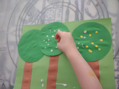 "Toddler Sprinkling the ""Apples"" (Hole Punch Circles) Onto Her Craft"