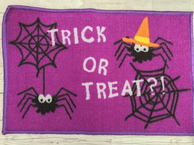 Purple Halloween doormat with 'trick or treat written on it', along with cartoon spiders and webs