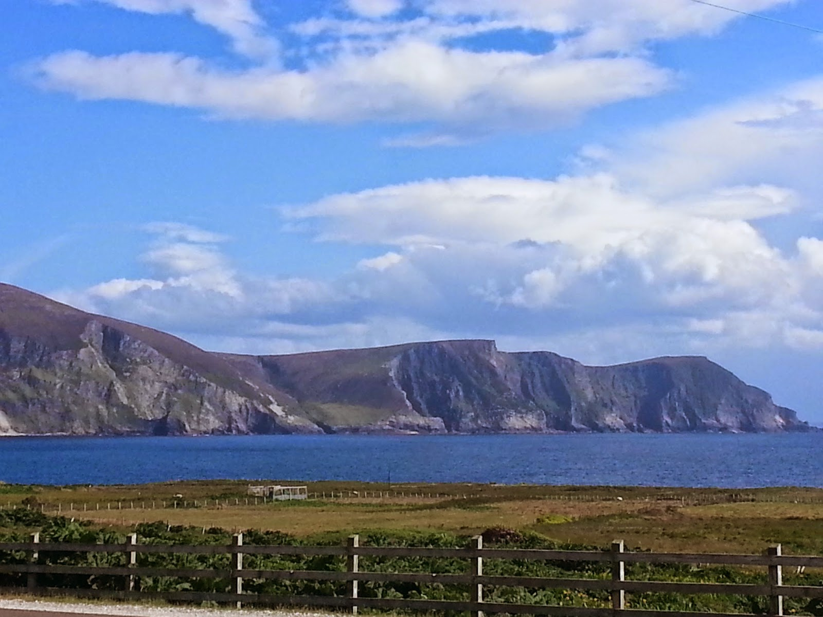 minaun cliffs achill island with beautiful blue sky and candy floss clouds