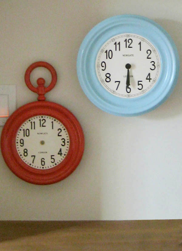 red and blue clocks hung on a white wall