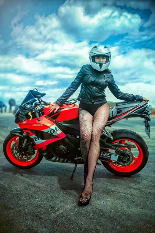 Tattooed girl poses with Repsol Honda CBR motorcycle