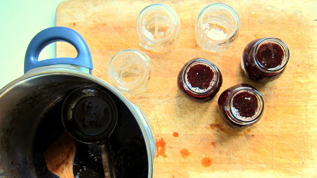 pressure cooker strawberry jam being ladeled into jars