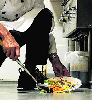 Chef scooping food into a plate