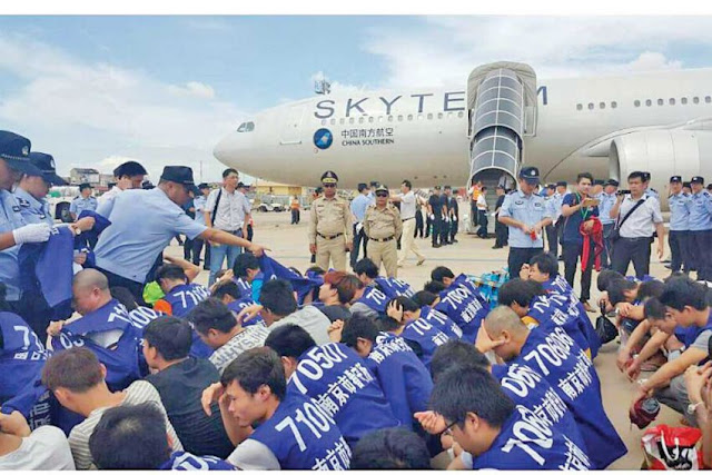 Chinese nationals sit on the tarmac at the Phnom Penh International Airport on Monday before being deported for their involvement in a VOIP scam. Photo supplied