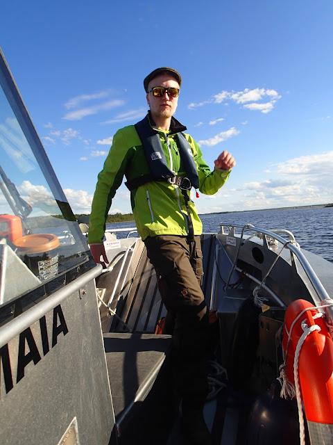 Mies paukkuliiveissä veneen kannella poseerausasennossa