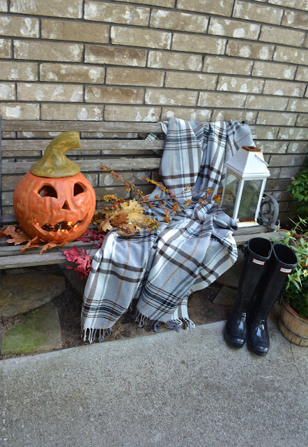 Hermine Throw on a Bench with Hunter boots and a Jackolantern.