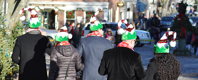 friends wearing Christmas hats taking the Christmas Stroll