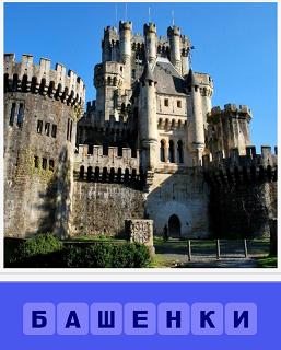 стоит старинный замок с разными башенками на верху