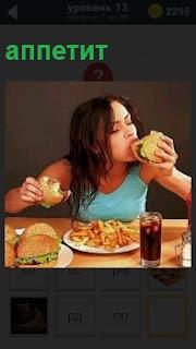 Девушка за столом аппетитно ест бутерброд с ветчиной и стакан с напитком на столе