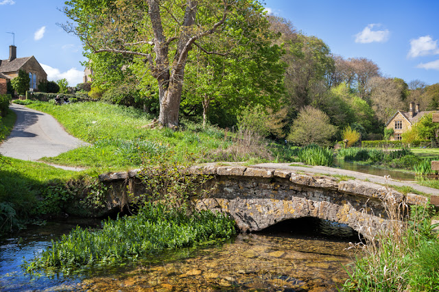 Idyllic view of Upper Slaughter and historic footbridge over a stream in the Cotswolds