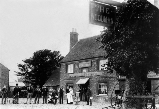 Photograph of The Woodman at Water End. Probably known as The Tollgate in 1700s. Purchased by Charles Bradshaw, a Hatfield baker and brewer in 1851, who sold out to Edward Pryor and Percy Reid in 1888. The premises were shown as a grocers shop as well as a beer retailer during the 19th century and in 1881 the licensee George Dickens also gave his occupation as a gardener. The 1891 census shows George Dickens (54) publican and labourer, Harriet Dickens (58) wife, and Annie Day (24) niece. c 1890