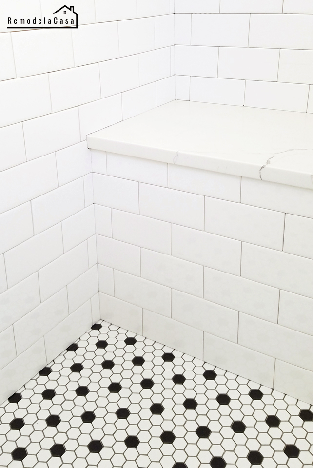 white bathroom with sitting bench, subway tile.
