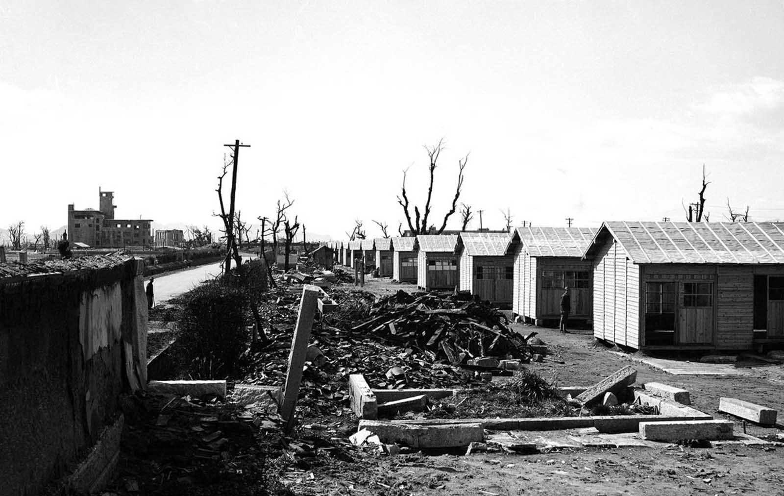 New buildings (right) rise out of the ruins of Hiroshima, Japan, on March 11, 1946. These single story homes built along a hard-surfaced highway are part of the program by the Japanese government to rebuild devastated sections of the country. At left background are damaged buildings whose masonry withstood the effects of the first atomic bomb ever detonated as a weapon.