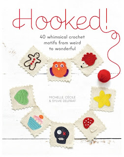 "Cover of the book ""Hooked!"" shows a string of bunting made of white crocheted squares. Each square has a crocheted motif applique. Appliques include an outlined gingerbread man, orange owl, red hedgehog, yellow starfish, red & white mushroom, black skull, blue & pink cupcake, green love heart. The title ""Hooked"" is displayed across the top with the subheading in smaller text underneath. The authors' names are in the centre of the page surrounded by the bunting. All on a white background."