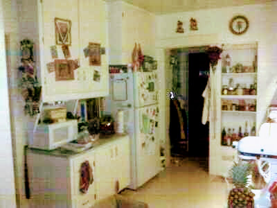 grainy photo of old and cluttered kitchen
