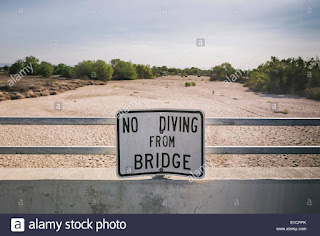 A sign cautions people not to dive from a bridge over the Kern River, which has been dried up by water diversion projects and prolonged drought, in Bakersfield, California. (Photo Credit: Scott London) Click to Enlarge.