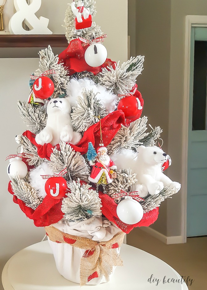 A flocked tree becomes a winter wonderland with Coca-Cola ornaments and fluffy polar bears. Read more about it at diy beautify.