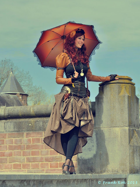 Women's Steampunk fashion in shades of orange/rust/brown. Skirt, bolero jacket, parasol/umbrella