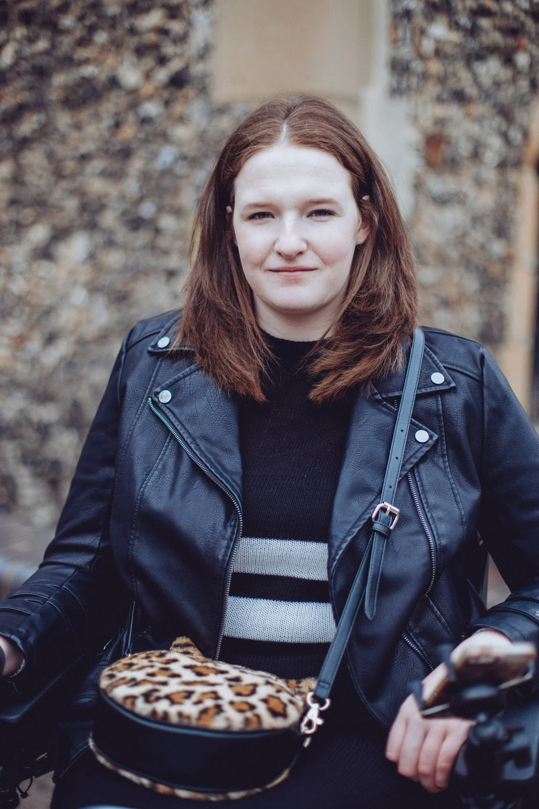 Up close image of Shona with a small smile on her face. Her hair is down and straight, she is wearing a black dress, leather look jacket and a leopard print bag.