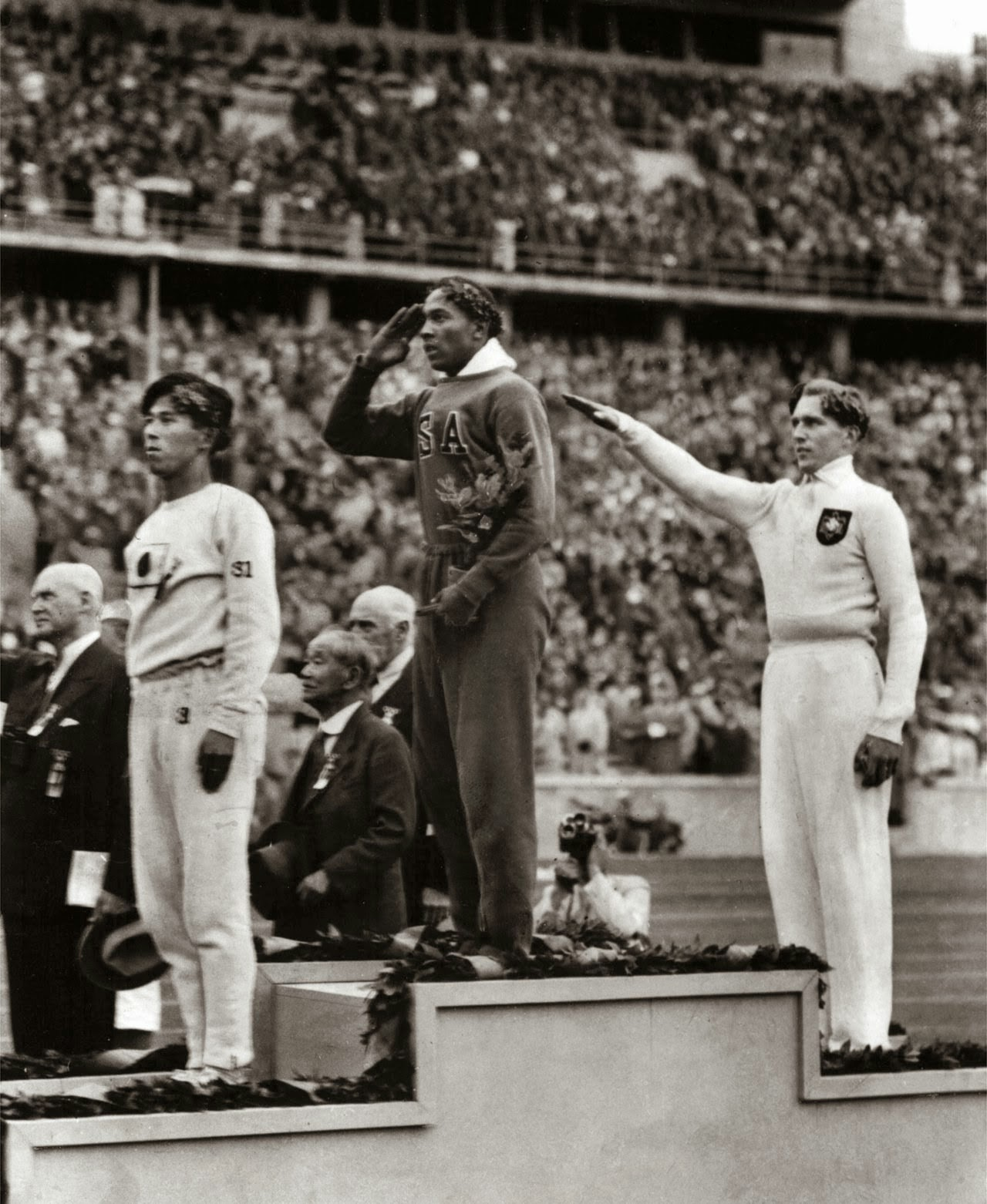 Jesse Owens salutes during the presentation of his gold medal for the long jump, after defeating Germany's Lutz Long during the 1936 Summer Olympics in Berlin.