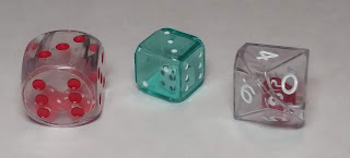 On the left is a large, hollow, clear plastic d6 with red pips, inside of which are two tiny red d6s with white pips. Beside that is a clear green plastic d6 with white pips, slightly larger than a normal d6, that is also hollow, and inside is a tiny white d6. On the right is a clear hollow d10 with white numbers, which has a small red d10 inside of it.