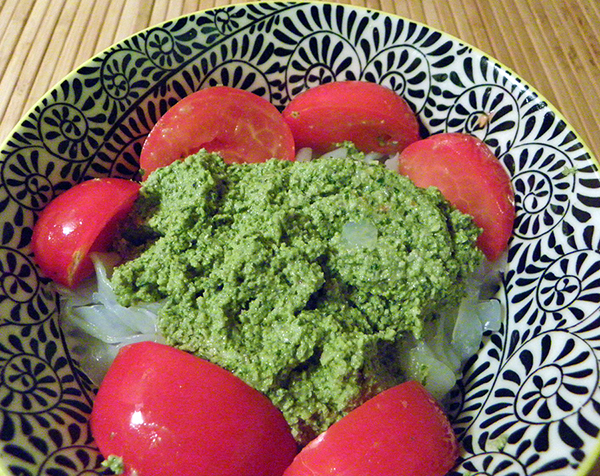 closeup of pesto topping shiritaki noodles, garnished with tomatoes
