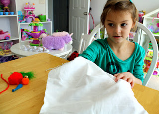 "I used a cloth bag instead of a box for the ""Touch is One of the Five Senses - Mystery Box"" activity. Tessa used her sense of touch to identify and describe the mystery items in the bag."