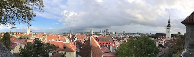 Panoramautsikt over en gamleby med røde tak og noen kirketårn som stikker opp.