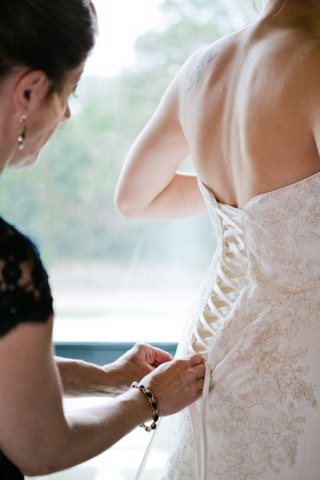 The mother of the bride laces up the brides wedding dress