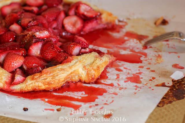 Image of a cut baked free form puff pastry pie with ooey gooey strawberries.