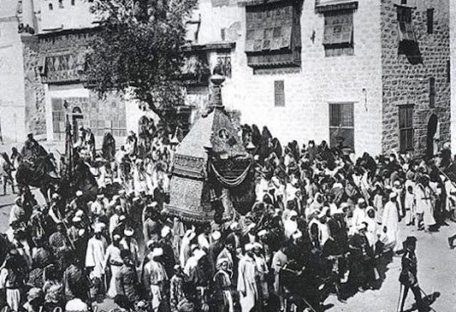 المحمل محمولاً عبر شوارع مكة المكرمة على ظهر جمل يأتي من القاهرة ودمشق أيام الحج 1914م