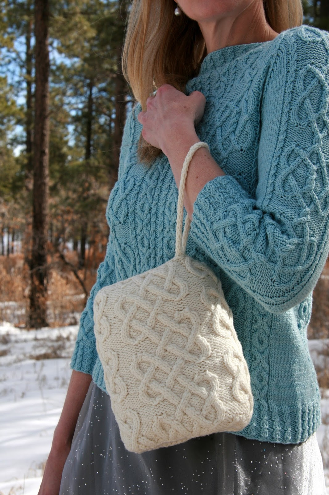 3b1a42b47048 Wrap your hands in love and Cormo with this cozy muff covered in  heart-shaped cables. Worked in one piece and finished with an i-cord wrist  strap