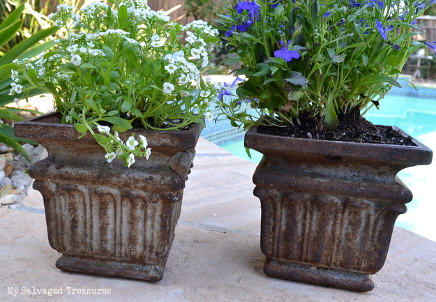 repurposed cast iron post bases used as flower pots