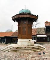 Saraybosna'daki bir meydanda üzerinde bir çeşme olan tarihi bir su sebili